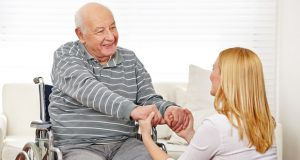 imagem da cuidadora cuidando de idoso a fim de obter a reabilitação de saúde